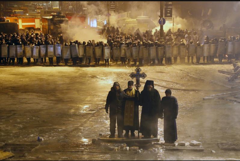 Kiev, Ukraine 01/24/2014 Orthodox priests prayed as they stood between pro-European Union activists and police lines.  Sergei Grits/AP