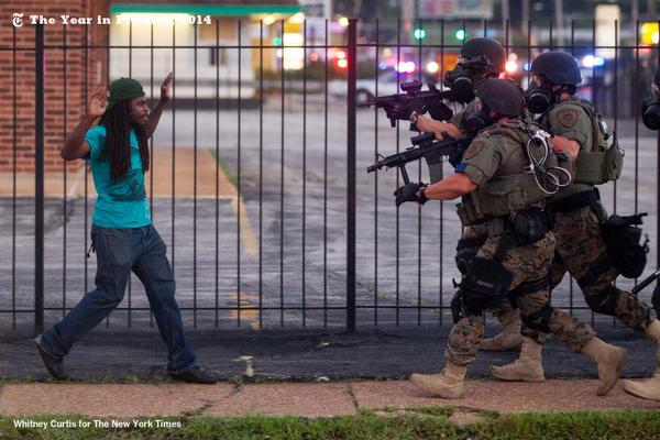 Ferguson, Missouri 08/11/2014 A man backed away from law enforcement officers at a demonstration in response to the police shooting of Michael Brown. Whitney Curtis for The New York Times